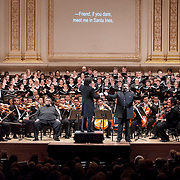 "December 12, 2012 - New York, NY : Conductor Gustavo Dudamel, on pedestal, leads the  Westminster Symphonic Choir and the Simón Bolívar Symphony Orchestra of Venezuela, along with baritone Gaspar Colón, standing at center right, as they perform Antonio Estévez's ""Cantata criolla"" at Carnegie Hall's Stern Auditorium / Perelman Stage on Tuesday evening.  CREDIT: Karsten Moran for The New York Times"