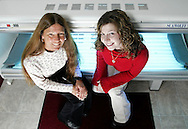 Owner Bonnie Miller and licensed nail technician Jennifer DeGroat sit on a tanning bed at Island Tan Spa in Port Jervis on. Nov. 30, 2006.