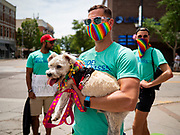 "28 JUNE 2020 - DES MOINES, IOWA: JEFF WOODS, front, and his dog, LOUIE, along with NAREN BHOJWANI and TANNER MOTE cheer during the Capitol City Pride Parade in Des Moines. Most of the Pride Month events in Des Moines were cancelled this year because of the COVID-19 pandemic, but members of the Des Moines LGBTQI community, and Capitol City Pride, the organization that coordinates Pride Month events, organized a community ""parade"" of people driving through the East Village of Des Moines displaying gay pride banners and flags. About 75 cars participated in the parade.       PHOTO BY JACK KURTZ"