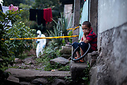 The outskirts of Tegucigalpa city, a boy watched investigators remove the body of a 21 year old woman neighbour after a brutal home invasion by a local gang. 4th August 2017.