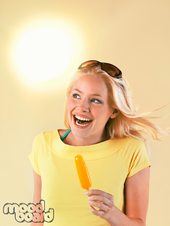 Smiling woman holding popsicle on hot Summer Day