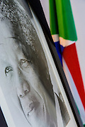 Brussels Belgium 6th December 2013. At the South African Embassy in Brussels people gather, Nelson Mandela died just yesterday.The portrait of Mandela and the South african flag