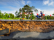 14 JULY 2015 - THAILAND:  A motorcyle is driven along a collapsed roadbed in Ayutthaya province. The drought that has crippled agriculture in central Thailand is now impacting residential areas near Bangkok. The Thai government is reporting that more than 250,000 homes in the provinces surrounding Bangkok have had their domestic water cut because the canals that supply water to local treatment plants were too low to feed the plants. Local government agencies and the Thai army are trucking water to impacted communities and homes. Roads in the area have started collapsing because of subsidence caused by the retreating waters. Central Thailand is contending with drought. By one estimate, about 80 percent of Thailand's agricultural land is in drought like conditions and farmers have been told to stop planting new acreage of rice, the area's principal cash crop.      PHOTO BY JACK KURTZ