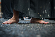 A barefoot nazareno in a street of Seville, Spain.