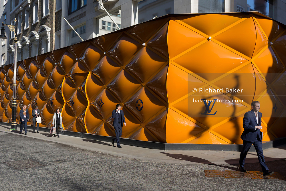 Passers-by and the temporary renovation hoarding of luxury brand Louis Vuitton in New Bond Street, on 25th February 2019, in London, England.