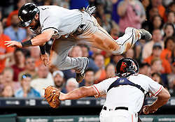 Chicago White Sox' Adam Eaton, top, leaps over Houston Astros catcher Evan Gattis after being tagged out in the third inning of a baseball game, Saturday, July 2, 2016, in Houston. (AP Photo/Eric Christian Smith)