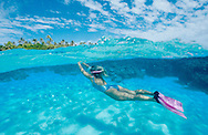 A woman enjoys snorkelling in clear blue waters off  Ha'apai islands, Tonga.