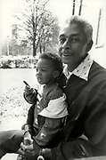 Israel Green holds his grandson, two year old Taveris Green,  Green. Green and a neighbor keep watch over their neighborhood at Atlanta's Techwood Homes public housing project. Armed with the bats, the two men hoped to keep the killer or killers of Atlanta's childern from their turf.