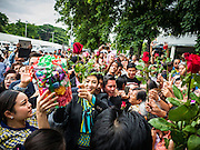 05 AUGUST 2016 - BANGKOK, THAILAND: YINGLUCK SHINAWATRA accepts flowers from people while she walks through a mob of supporters at the Supreme Court of Thailand Friday. She appeared in court to start her legal defense. She was deposed by a military coup in 2014 and is being tried on corruption and mismanagement charges related to a price support plan for Thai rice farmers that was instituted while she was Prime Minister. More than two years after her government was deposed by a military coup, she is still a popular figure and hundreds of her supporters packed the area around the courthouse to greet her when she arrived at the Court.        PHOTO BY JACK KURTZ