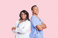 Portrait of confident mixed race male and female surgeons over pink background