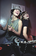 DJ's Queens of Noize, laughing by a set of decks, UK 2000's