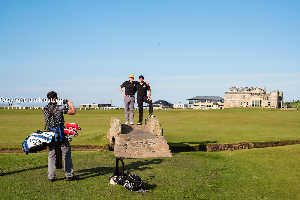 Golfers posing for photograph on Swilken Burn Bridge on fairway of 18th hole at Old Course in St Andrews in Fife , Scotland, United Kingdom