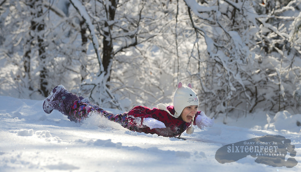 Gary Cosby Jr./Decatur Daily   Snow blankets the Tennessee Valley Thursday morning after a snow that began late Wednesday and fell through much of the night.  Audrey Burleson takes a thrill ride down a big hill on Colony Lane in Hartselle.