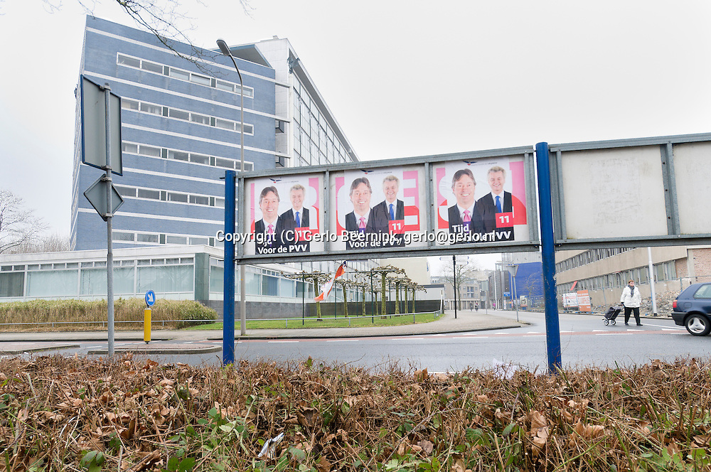 Nederland, Almelo, 20110225..Naast het gemeentehuis in Almelo hangen de affiches van de PVV op de achterkant van de verkiezingsborden. Affiches voor de komende provinciale verkiezingen. Naast de provinciale kandidaat Geert Wilders ook op het affiche. Op de voorgrond verdorde bladeren aan de struiken...Netherlands, Almelo, 20110225. ? addition to the city hall in Almelo hang the posters of the PVV on the back of the election boards. Posters for the upcoming provincial elections. Besides the provincial candidate Geert Wilders on the poster. In the foreground withered leaves on the bushes.