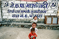 Children play in the street of pokhara in front of a Maoist graffiti