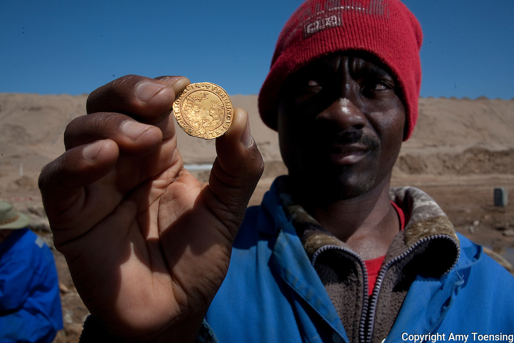 ORANJEMUND, NAMIBIA -- OCTOBER 01: Namdeb mine worker holds one of the 3 Excellentes coins, which display inscriptions of King Ferdinand and Queen Isabella, known for uniting Spain in the early 1500s found on October 01, 2008 in Oranjemund, Namibia. The wreck was uncovered by miners in the Namdeb diamond mine off the coast of Namibia. The ship was found seven meters below sea level on April 1, 2008. Archeologists presume the wreck is from the early 1500s. Most of the the artifacts found are being stored in a storage shed at the Namdeb Diamond Mine. Items include: copper ingots, bronze canons, canon balls, pewter bowls and plates, ivory tusks from African elephants, and most substantial over 2000 gold coins - approximately 21 kg - the most gold found in Africa since the Valley of the Kings in Egypt. (Photo by Amy Toensing) _________________________________<br /> <br /> For stock or print inquires, please email us at studio@moyer-toensing.com.