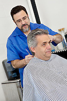 Barber cutting hair of mature male customer