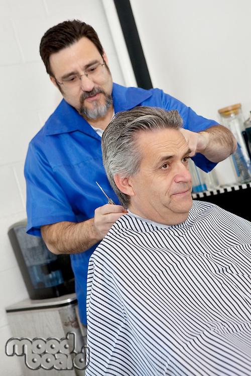 Barber cutting hair of mature male customer