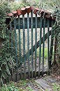 gate in garden fence with rusty cans placed on top