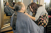 gbs121213b/ASEC -- Audrey Morelock trims the goatee of her father, John Morelock, before cutting off his long hair  at the Hair Addict salon on Thursday, December 12, 2013. The braided locks with be donated to Pantene Beautiful Lengths which gives free wigs to adult cancer victims.(Greg Sorber/Albuquerque Journal)