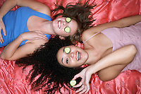 Teenage Girls lying on backs on pink sheets with cucumbers in eyes overhead view