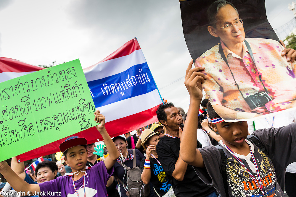 24 NOVEMBER 2013 - BANGKOK, THAILAND:     Royalist anti-government protestors carry a photo of Bhumibol Adulyadej, the King of Thailand, during a protest on Ratchdamnoen Ave in Bangkok. More than 400,000 people packed onto Ratchdamnoen Ave in Bangkok Sunday, continuing an anti-government protest that started weeks ago over a blanket amnesty bill passed by the Thai Parliament. The amnesty bill was defeated in the Thai Senate and the protest morphed into a general protest against the government. The protestors are allied with the Thai Democrat party, the opposition party in parliament. Tens of thousands of pro-government Red Shirts have come to Bangkok to defend the government and are rallying in a different part of the city. Police have warned of clashes between the two groups but as of Sunday evening no problems had been reported. The protestors allege that the amnesty would allow fugitive former Prime Minister Thaksin Shinawatra to return to Thailand.        PHOTO BY JACK KURTZ