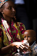 A malnourished refugee child from Central African Republic eats Plumpy Nut therapeutic food while sitting on her mothers's lap at the Garga Sarali integrated health center in the town of Garga Sarali, near Bertoua, Cameroon, on Tuesday September 15, 2009.