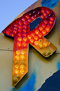 "The letter ""R"" glows from a carnival marquee at dusk on a summer evening."