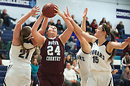 North Country's Kylie Wright (24) leaps between MMU's Lexi Mousley (15) Ellie Devereux (1) and Madi Laughlin (21) for a lay up during the girls basketball game between the North Country Falcons and the Mount Mansfield Cougars at MMU high school on Monday night February 15, 2016 in Jericho. (BRIAN JENKINS/for the FREE PRESS)