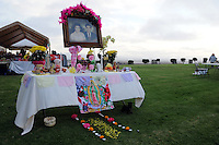 """An """"ofrenda,"""" or altar, set up at the crest of the hill. In a touching final celebration of All Soul's Day on Saturday night, hundreds of congregants came to Queen of Heaven Cemetery in Salinas to attend mass, offer their prayers, and as dusk fell, participate in a candlelight procession.  Friends and family members sat by the graves of loved ones, many of which were decorated with traditional Day of the Dead marigolds, photographs of the departed, and things that were their favorites in life."""