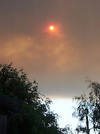 Thick smoke from a wildfire nearly blocks out the morning sun, as seen through a bedroom window in Monterey, California