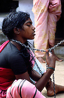 TAMIL NADU, MARCH 1994.A young woman is sitting on the floor looking at her chains..This is the fate awaiting those who the locals believe are possessed by evil spirits.