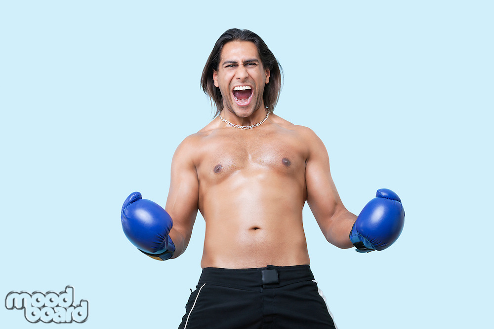 Portrait of young Asian boxer screaming over blue background
