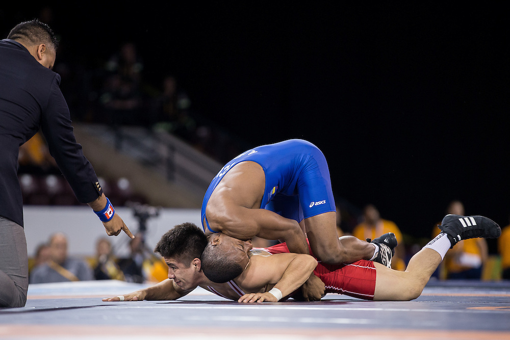 Andres Montano (top) of Ecuador tries to get leverage on Ali Soto of Mexico during their gold medal bout in the 59kg weight class of the men's greco-roman wrestling at the 2015 Pan American Games in Toronto, Canada, July 15,  2015.  AFP PHOTO/GEOFF ROBINS