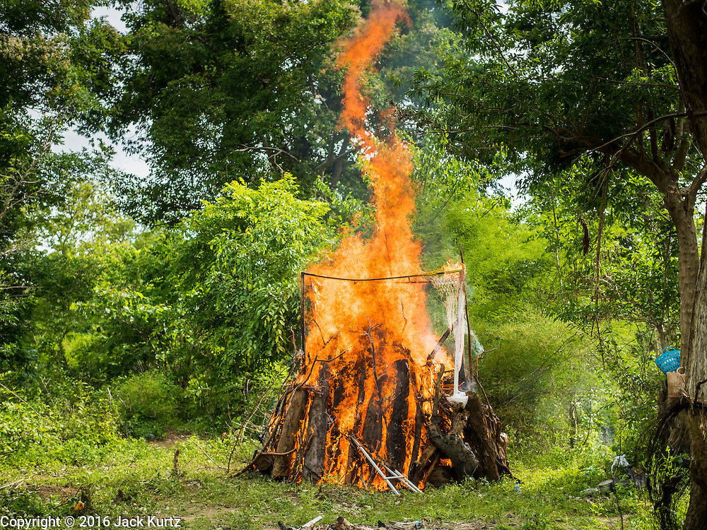 20 JUNE 2016 - DON KHONE, CHAMPASAK, LAOS:  The funeral pyre of a man who died in Don Khone village on Don Khone Island. Don Khone Island, one of the larger islands in the 4,000 Islands chain on the Mekong River in southern Laos. The island has become a backpacker hot spot, there are lots of guest houses and small restaurants on the north end of the island. In the southern Lao funeral tradition, the deceased is cremated at the place of his choosing, usually a place he (or she) was especially fond of. In this case, the man chose to be cremated in a small clearing in the jungle a few kilometers from his home.    PHOTO BY JACK KURTZ