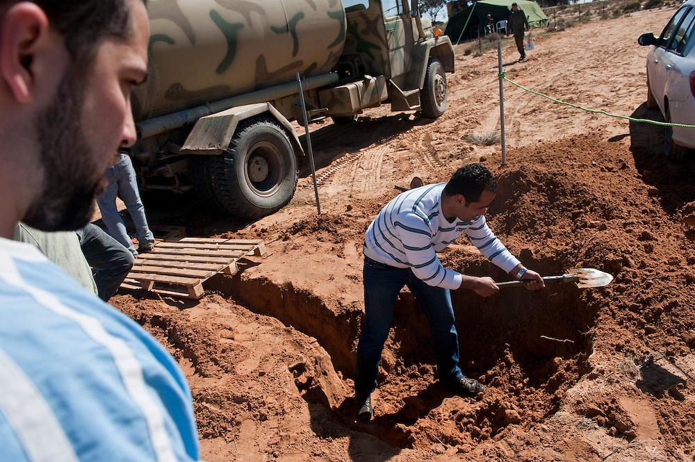 Des bénévoles Tunisiens s'affairent en coopération avec l'armée a creuser un trou pour l'évacuation des eaux usées au camp humanitaire Choucha. Plus de 140 000 réfugiés ont déjà quitté la Libye par la Tunisie ou l'Egypte et des milliers continuent d'arriver chaque jours. Mercredi 2 Mars 2011, camp humanitaire Choucha, Tunisie..© Benjamin Girette / AP