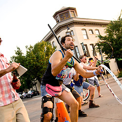 Spectators using bike parts as instruments cheer on racers during the Fat Tire Crit of the Grand Junction Off-Road Friday.  <br /> Photos by Brian Leddy