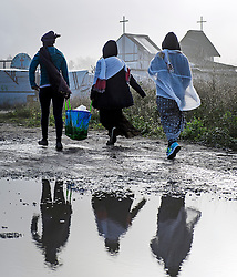 © Licensed to London News Pictures. 23/10/2016. Calais, France. A group of women migrants carry food in a bag through the camp. Daily life continues as preparations begin for the demolition of the migrant camp in Calais, France, known as the 'Jungle'. French authorities have given an eviction order to thousands of refugees and migrants living at the makeshift living area of the French coast. Photo credit: Ben Cawthra/LNP