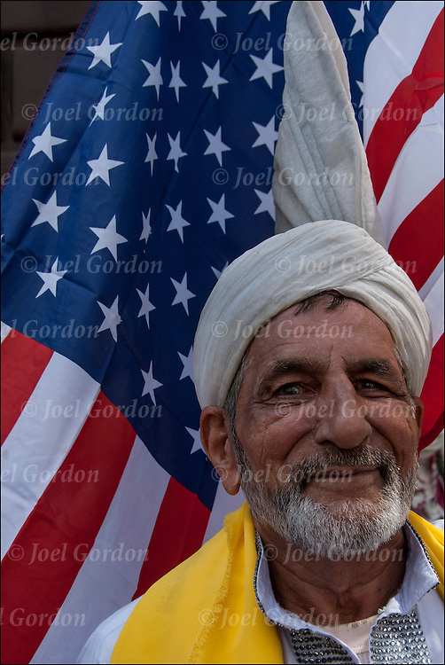 Pakistani American Pride, elderly man in white turban and traditional regalia with  American flag in background.<br />