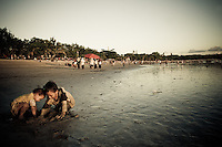 Two children dig in the sand at Kuta Beach, Bali, Indonesia.
