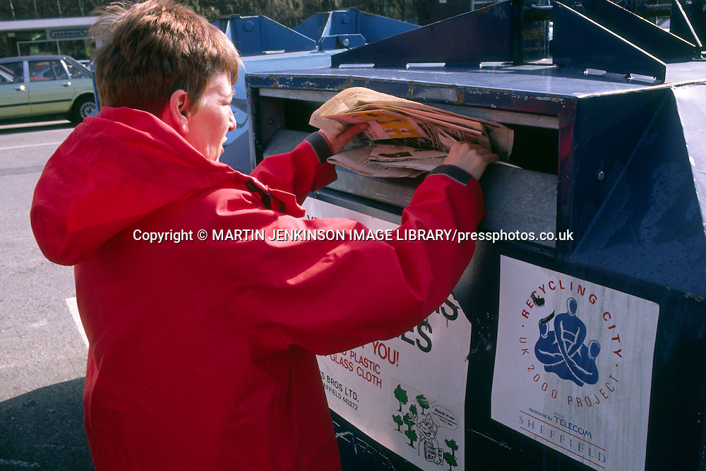 Women putting newspapers into a recycling container ....