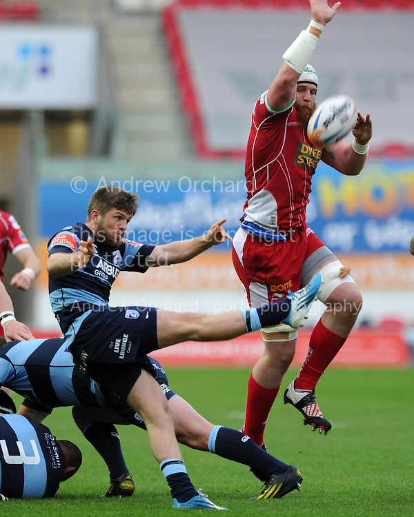 Jake Ball of the Scarlets &reg; tries to charge down the kick from Cardiff Blues Lewis Jones. Rabodirect Pro12 rugby union match, Scarlets v Cardiff Blues at Parc y Scarlets in Llanelli, South Wales on Sat 10th May 2014.<br /> pic by Andrew Orchard, Andrew Orchard sports photography.