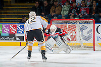 KELOWNA, CANADA - OCTOBER 25: Jackson Whistle #1 of Kelowna Rockets defends the net against a penalty shot from Jesse Gabrielle #12 of Brandon Wheat Kings on October 25, 2014 at Prospera Place in Kelowna, British Columbia, Canada.  (Photo by Marissa Baecker/Shoot the Breeze)  *** Local Caption *** Jackson Whistle; Jesse Gabrielle;
