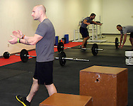 (from left) Owner Jason Hoskins of Dayton, Chad Banter of Centerville and Kerry Penner of Dayton during a workout of the day session at Vigor Crossfit in Moraine, Wednesday, January 25, 2012.