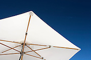 Sun umbrella on the beach at the Bora Bora Nui Resort & Spa. Previously a Starwood Luxury Collection property, the Bora Bora Nui is now operated by Hilton. Bora Bora is one of the Leeward Islands in the Society Islands archipelago of French Polynesia.