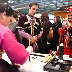 Milan, Italy - February  17: A dancer from Azerbaijan takes a picture at a korean woman at BIT International Tourism Exchange on february 17, 2012 in Milan, Italy.