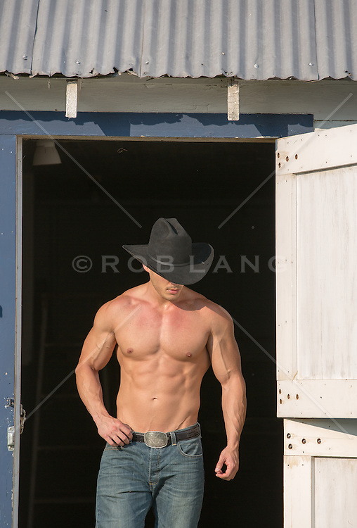 shirtless muscular cowboy on a ranch