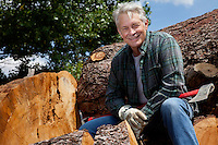 Smiling senior man sitting on logs