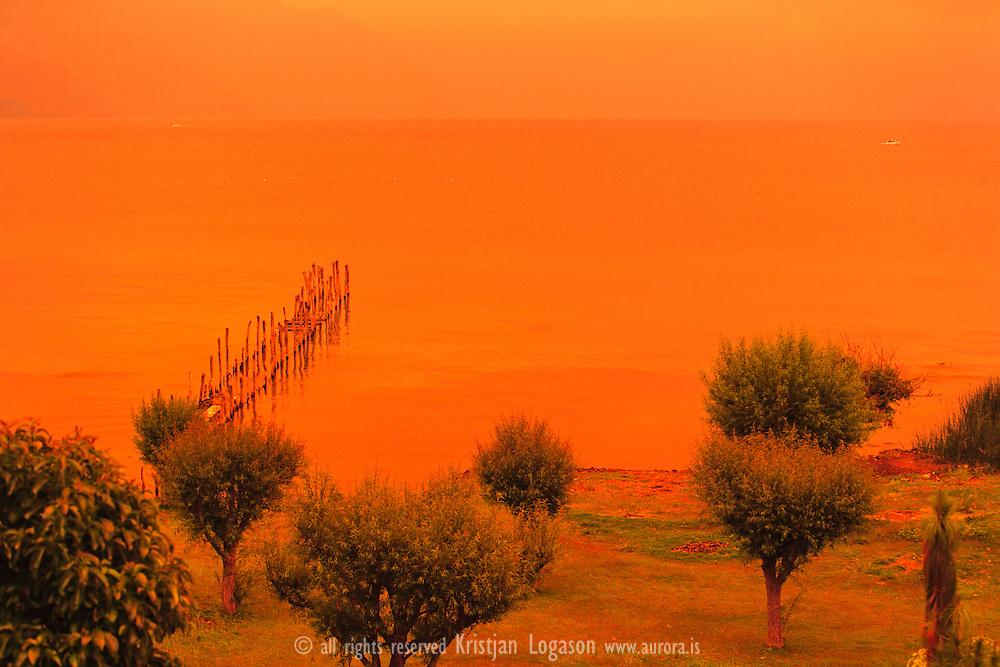 Orange glowing lake atitlan in Guatemal as the sun sends orange colored rays through clouds and fog