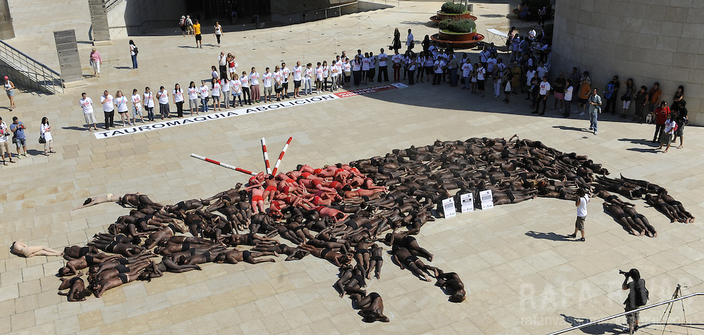Members of Anima Naturalis, Equanimal foundation and CAS-International pro animal groups create a giant bull shape with their bodies covered in paint during a protest against bullfighting in front of the Guggenheim Bilbao museum, in the Northern Spanish Basque city of Bilbao, on August 21, 2010, ahead of the Aste Nagusia festivities.  PHOTO / Rafa Rivas